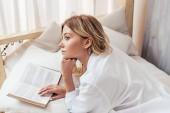 Nachdenkliches Mädchen im Pyjama liest morgens zu Hause im Bett Buch