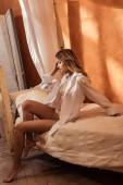 hezká mladá žena v prádle a bílé tričko pózuje na posteli