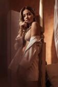 schöne junge Frau in weißem Hemd und Spitzenunterwäsche posiert in Bettnähe