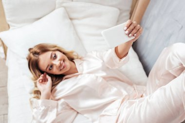 selective focus of blonde girl taking selfie on smartphone in bed during morning time at home
