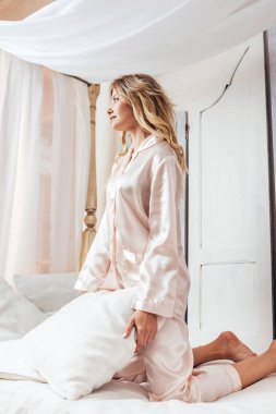 low angle view of blonde girl in pajama having fun with pillow in bed at home
