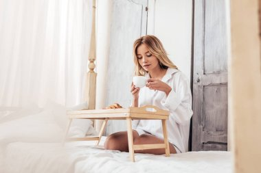 Selective focus of young blonde woman holding coffee cup while sitting on bed with breakfast on tray stock vector