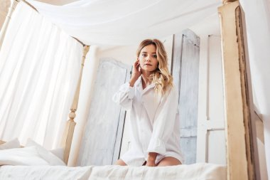 low angle view of pretty woman in white shirt posing in bed at home