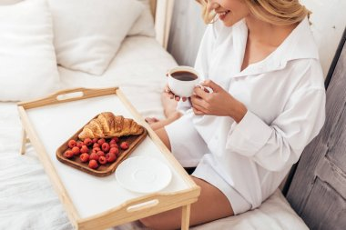 partial view of smiling girl holding coffee cup while sitting on bed with breakfast on tray