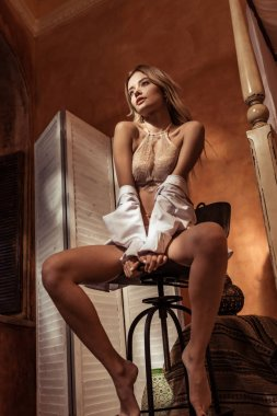 low angle view of woman in white shirt and lace lingerie posing on chair
