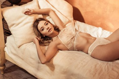 blonde girl wearing seductive lace lingerie and posing in bed