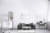 moderní interiér obývacího pokoje s postýlkou a pohovkou