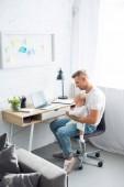 Vater sitzt am Computer-Schreibtisch, benutzt Smartphone und hält kleine Tochter im Wohnzimmer