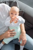 father sitting on couch and holding adorable baby with bottle at home