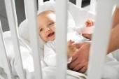 oříznutý pohled na tátu uvedení veselé miminko do dětské postýlky