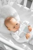 Fotografia ragazzino sveglio che tiene smartphone in culla bianca