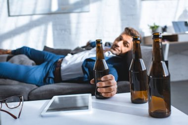 selective focus of bottle in hand of drunk businessman lying on sofa