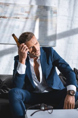 drunk businessman holding bottle and sitting on sofa in living room
