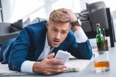 Šokovaný podnikatel při pohledu na smartphone a leží na koberci u skla s pitím alkoholu
