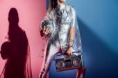 Fotografie oříznutý pohled módní ženy v stříbrné kombinézu a pláštěnka pózuje s boombox a disco koule na růžové a modré pozadí
