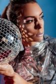 Fotografie atraktivní mladá žena pózuje s stříbrné disco koule na modrém pozadí