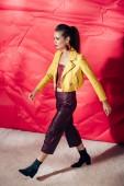 atraktivní módní dívka pózuje v žluté kožené bundě na červeném pozadí pro módní střílet