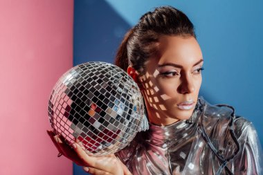 beautiful stylish young woman posing with silver disco ball on pink and blue background