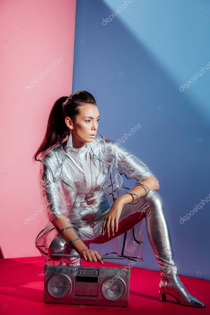 Fashionable young woman in silver bodysuit and raincoat posing with boombox on pink and blue background stock vector