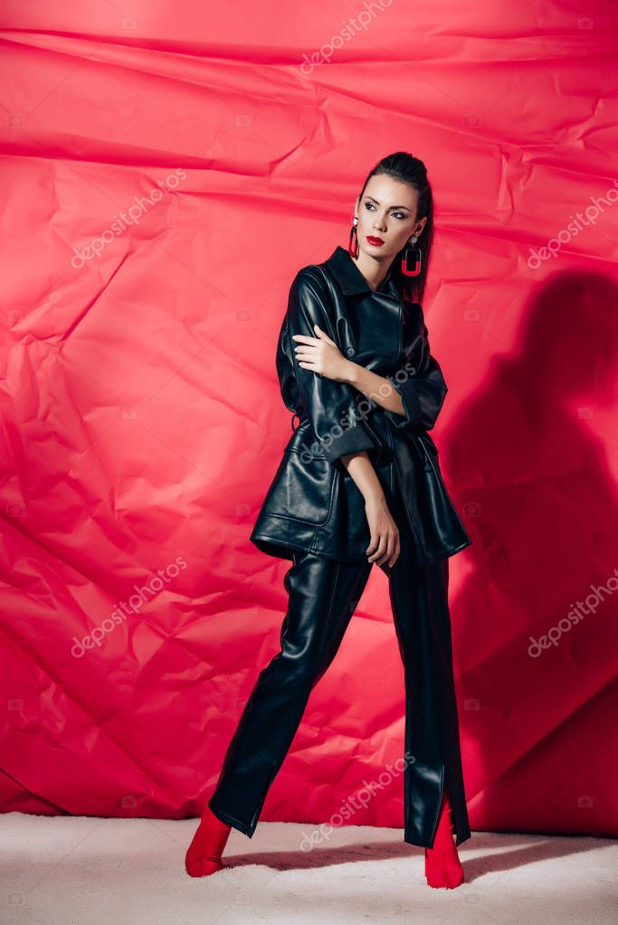Beautiful fashionable woman posing in black leather suit on red background stock vector