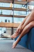 nízké část žena dotýkat se na vlastní nohy zatímco sedí na posteli v ranní době doma