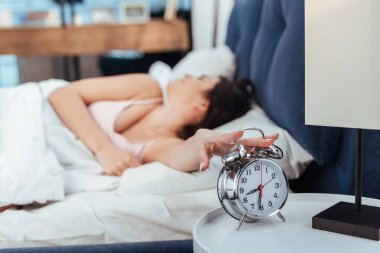 Selective focus of girl turning off alarm clock in bedroom during morning time at home stock vector