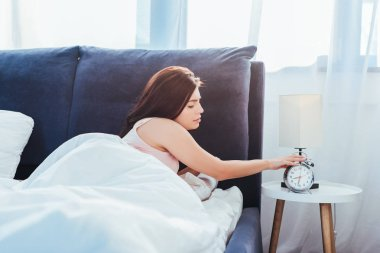 side view of young woman turning off alarm clock in bedroom during morning time at home