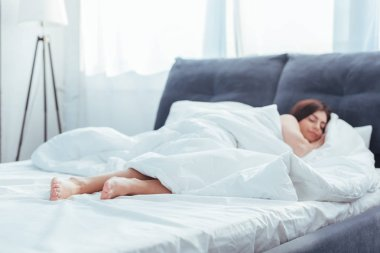 selective focus of girl sleeping in bed during morning time at home