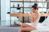 boční pohled na mladou ženu sedící s šálek kávy na posteli doma v době ranní