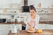 Fotografie hezká mladá žena oranžová řezání nožem na dřevěné desce v kuchyni