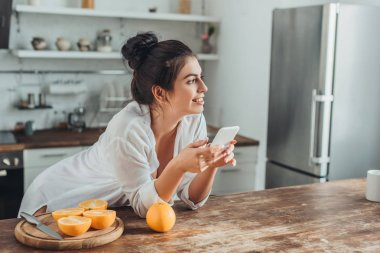 Cheerful young woman using smartphone at wooden table with oranges in kitchen at home stock vector