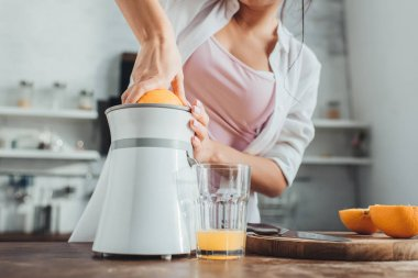 partial view of girl making fresh orange juice with juicer at wooden table in kitchen