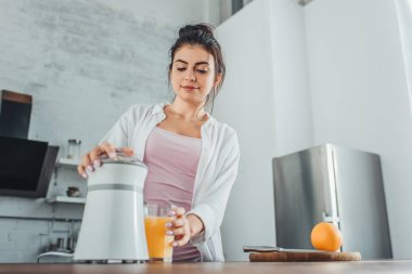 low angle view of girl making fresh orange juice with juicer at wooden table in kitchen