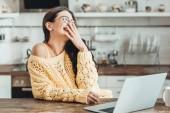 Selektivní fokus smějící se ženské volné noze sedět u dřevěného stolu s notebookem a kávy cup v kuchyni doma