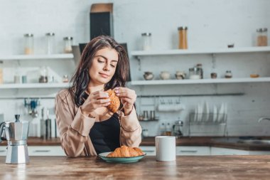 Young beautiful woman having breakfast with croissants and coffee at wooden table in kitchen at home stock vector