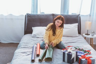 Selective focus of beautiful young woman packing gift while sitting on bed at home stock vector