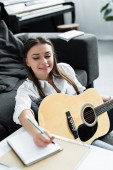 smiling girl with acoustic guitar writing in notebook while composing music at home