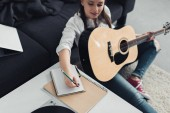 Fotografia ragazza con la chitarra acustica che si siede sul pavimento e scrittura in taccuino durante la composizione di musica a casa