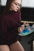 beautiful girl in burgundy sweater sitting, holding paintbrush, palette and painting at home