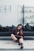 gyönyörű tervező ül a szőnyegen közelében a kanapén, és a gazdaság ceruza és notebook otthon