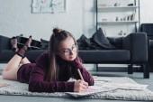 Fényképek vonzó tervező feküdt a szőnyegen, és a nappaliban ceruzával vázlat