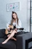 musicista sorridente che si siede sul divano e suonare la chitarra acustica a casa