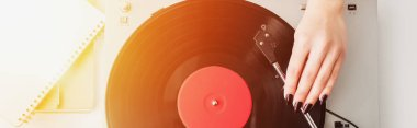 cropped view of woman playing vinyl record on vintage player