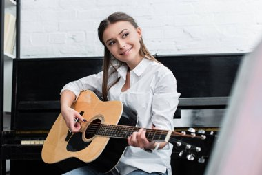 smiling girl sitting and playing guitar in living room with piano on background