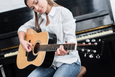 girl sitting and playing guitar in living room with piano on background