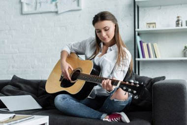 focused girl sitting on couch and playing guitar in living room