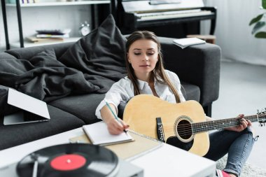 selective focus of girl with acoustic guitar writing in notebook while composing music at home
