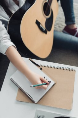 cropped view of girl with acoustic guitar writing in notebook while composing music at home