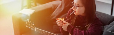 girl lighting marijuana joint and holding guitar at home with backlit and copy space