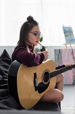 attractive girl sitting on couch, lighting marijuana joint and holding guitar at home